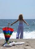 Jeune femme appréciant sur une plage images stock