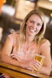 Jeune femme appréciant une bière à un bar Photo stock