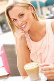 Jeune femme appréciant la cuvette de café Photos stock