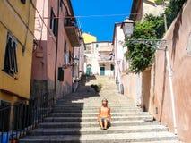 Jeune femme appréciant le soleil dans une allée d'un petit village médiéval rural Images libres de droits