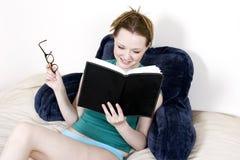 Jeune femme appréciant un livre Image stock