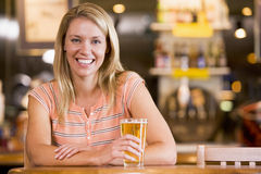 Jeune femme appréciant une bière à un bar Photos libres de droits