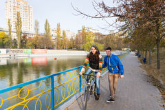 Jeune femme apprenant à monter le vélo sur le pont de parc Images libres de droits