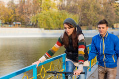 Jeune femme apprenant à monter le vélo sur le pont de parc Photographie stock