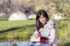 Jeune femme apprenant avec son chien en parc d'automne Photographie stock