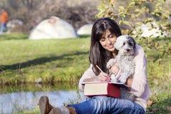 Jeune femme apprenant avec son chien en parc d'automne Images stock