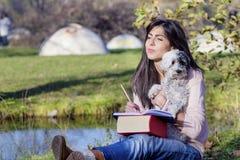 Jeune femme apprenant avec son chien en parc d'automne Image stock