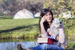 Jeune femme apprenant avec son chien en parc d'automne Images libres de droits