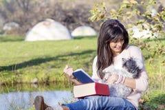 Jeune femme apprenant avec son chien en parc d'automne Photographie stock libre de droits