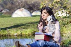 Jeune femme apprenant avec son chien en parc d'automne Photo libre de droits