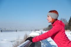 Jeune femme après que la course se repose sur le bord de mer et examine le distanc image libre de droits
