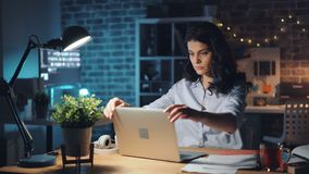 Jeune femme arrêtant l'ordinateur portable et la lumière dans le bureau la nuit et quittant le travail clips vidéos