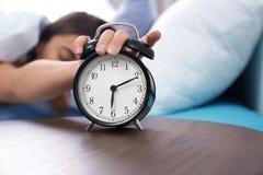 Jeune femme arrêtant le réveil dans le matin photos libres de droits
