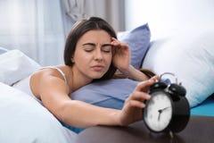 Jeune femme arrêtant le réveil dans le matin photographie stock