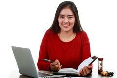 Jeune femme asiatique écrivant la note tout en vérifiant le graphique de volume de vente image stock