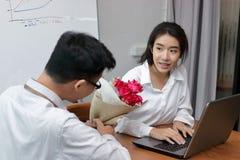 Jeune femme asiatique étonnée obtenant un bouquet des roses rouges dans le bureau le jour du ` s de valentine Histoires d'amour d Image libre de droits