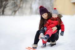 Jeune femme asiatique aidant le garçon caucasien d'enfant en bas âge avec son habillement d'hiver photo stock