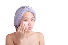 Jeune femme asiatique appliquant la crème sur son visage sur le blanc image stock