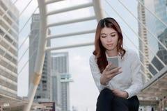 Jeune femme asiatique attirante à l'aide du téléphone intelligent mobile au fond urbain avec l'espace de copie Concept de la vie  images stock