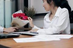 Jeune femme asiatique attirante étonnée acceptant un bouquet des roses rouges de l'ami dans le bureau le jour du ` s de valentine Photographie stock
