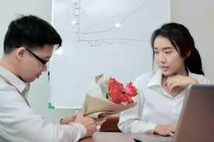 Jeune femme asiatique attirante acceptant un bouquet des roses rouges de l'ami dans le bureau le jour du ` s de valentine Histoir Image stock