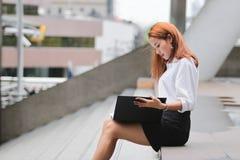 Jeune femme asiatique attirante d'affaires regardant des fichiers document dans des mains dehors Image stock