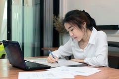 Jeune femme asiatique attirante d'affaires travaillant avec l'ordinateur portable sur le lieu de travail dans le bureau Photos libres de droits