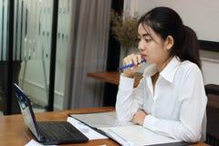 Jeune femme asiatique attirante d'affaires travaillant avec l'ordinateur portable sur le lieu de travail dans le bureau Photos stock