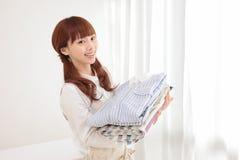 Jeune femme asiatique avec la blanchisserie photographie stock libre de droits