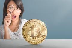 Jeune femme asiatique avec la loupe regardant le bitcoin d'or Photographie stock