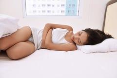 Jeune femme asiatique avec le confort dans le lit image libre de droits