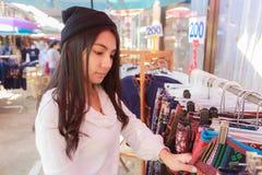 Jeune femme asiatique choisissant des vêtements dans le maket de rue image stock