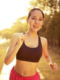 Jeune femme asiatique courant en parc Photo stock
