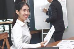 Jeune femme asiatique d'affaires de direction regardant l'appareil-photo entre écouter la présentation à l'arrière-plan moderne d photo stock