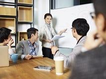 Jeune femme asiatique d'affaires facilitant une discussion Photo stock