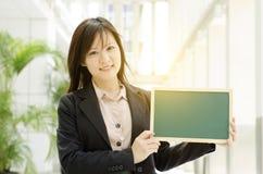Jeune femme asiatique d'affaires montrant le conseil vide Photographie stock libre de droits
