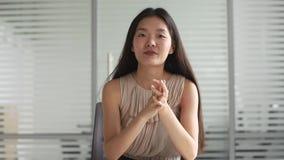 Jeune femme asiatique d'affaires regardant parler de caméra ou de webcam banque de vidéos