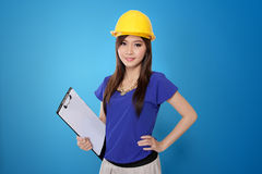 Jeune femme asiatique d'architecte dans le casque antichoc jaune, sur le fond bleu vibrant Images stock