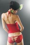 Jeune femme asiatique dans la lingerie rouge sexy par derrière Photos stock