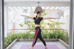 Jeune femme asiatique dans la relaxation ?tirant la position sur son plancher de balcon image stock