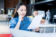 Jeune femme asiatique dans le bureau moderne photos libres de droits