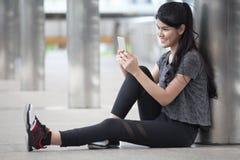 jeune femme asiatique de forme physique faisant une pause après la séance d'entraînement s'exerçant utilisant le smartphone sur l photographie stock