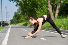 Jeune femme asiatique de forme physique ?tirant des jambes apr?s course portrait de sport d'extérieur image stock