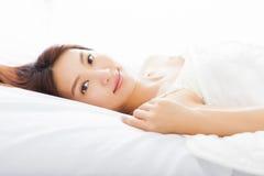 Jeune femme asiatique dormant dans le lit Image libre de droits