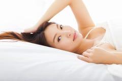 Jeune femme asiatique dormant dans le lit Photos libres de droits