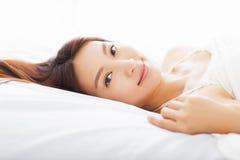 Jeune femme asiatique dormant dans le lit Images stock