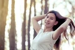 Jeune femme asiatique effleurant ses cheveux et appréciant la nature photos stock