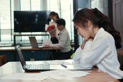 Jeune femme asiatique fâchée envieuse d'affaires travaillant avec les couples affectueux dans l'amour à l'arrière-plan de bureau  Photo libre de droits