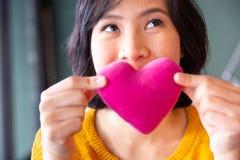 Jeune femme asiatique faisant le baiser d'air à un coeur rose Image stock