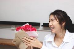 Jeune femme asiatique gaie acceptant un bouquet des roses rouges de l'ami dans le bureau le jour du ` s de valentine Histoires d' Images libres de droits